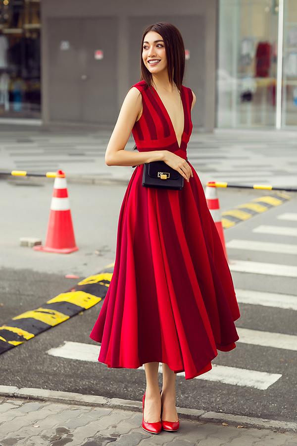 Dáng váy xoè cổ điển được nhà mốt Việtlàm mới với đường xẻ ngực sâu cùng sự kết hợp hai tông màu sáng, tối với cùng sắc đỏ thú vị. Người đẹpphối trang phục cùng chiếc túi thắt ngang eo lạ mắt.