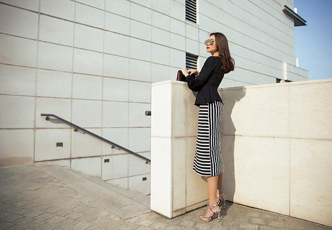Áo chít eo được kết hợp cùng chân váy kẻ sọc trắng đen giúp người mặc có được nét gợi cảm và năng động.