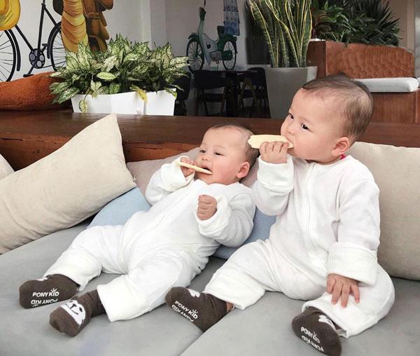 Hai anh em sẽ ngồi ngoan khi được cho ăn bánh và xem ca nhạc. Ảnh: NVCC.