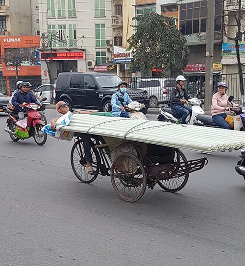 Ông cụ nằm ngửa đạp xe xích lô chở tôn nhựa