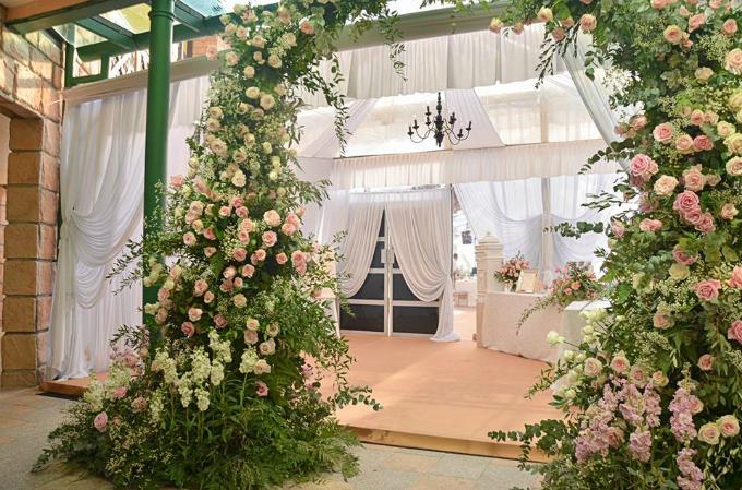 Khu vực cổng chào và bàn lễ tân đón tiếp khách mời tràn ngập hoa tươi.