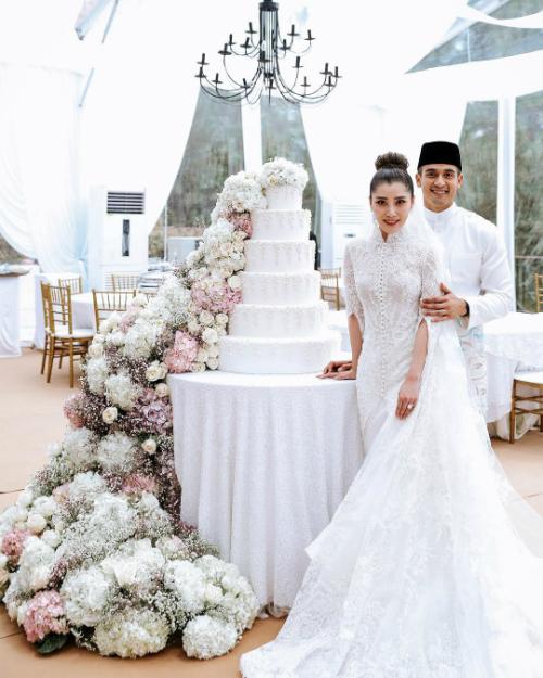 Sau phần nghi thức, cô dâu và chú rể thay đổi trang phục sang màu trắng. Trong khi chú rể vẫn mặc đồ truyền thống là chiếc Baju Melayu với những họa tiết thêu màu xanh nhạt và nâu...