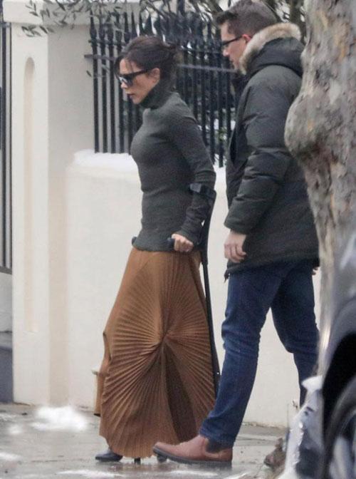 Vic đi giày cao gót, tay chông nạng rời biệt thự ở London, Anh, hôm 3/3.