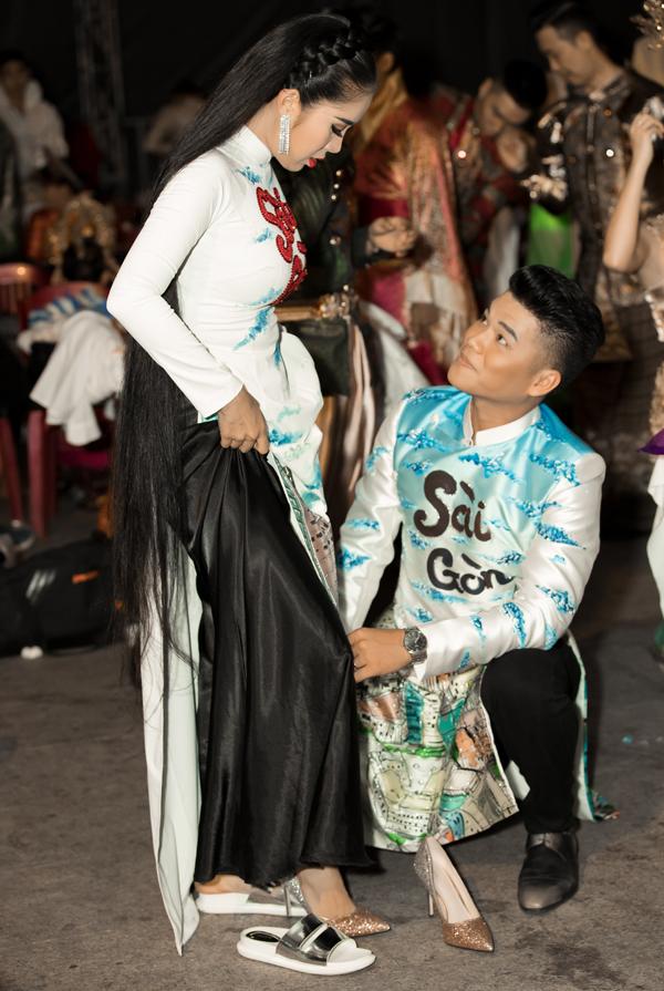 Chồng trẻ ân cần cúi xuốnggiúp nữ diễn viên mang giày cao gót.