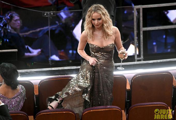 Người đẹp lười đi lòng vòng mà vén váy trèo thẳng qua ghế trong khi nhiều đồng nghiệp đã ngồi xung quanh. May mắn, bộ đầm Dior mà J.Law đang mặc không gặp sự cố nào khi bị cô chủ đối xử phũ phàng.