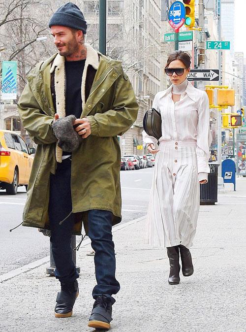 Vợ chồng Becks người đi trước, người đi sau khi rời khách sạn. Cựu danh thủ Anh mặc áo khoác lông ấm áp còn Vic trông có vẻ mong manh với bộ váy sơmi nằm trong bộ sưu tập thời trang mới nhất.