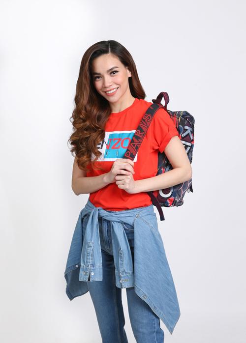 Hà Hồ chọnset đồ năng động với T-shirt màu đỏ, áo jean cột nhẹ quanh hông kết hợp balo Kenzo cá tính.