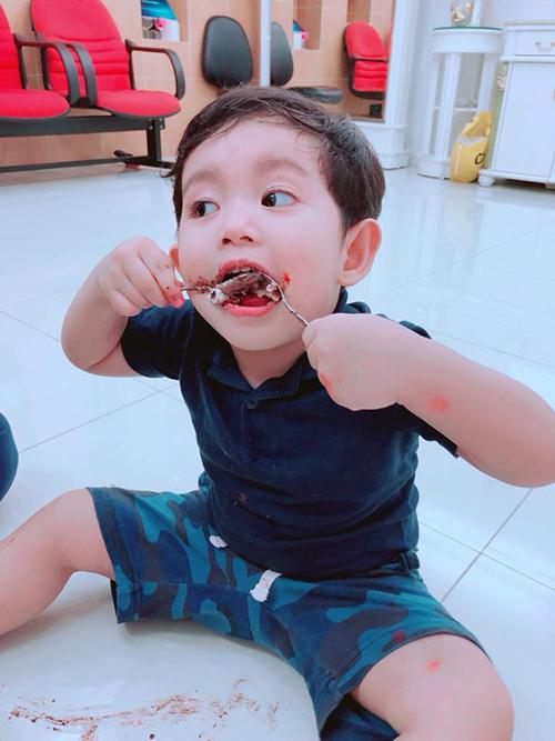 Kubi nhà Khánh Thi Phan Hiển ăn bánh say sưa, không cần đến sự trọ giúp của bố mẹ.