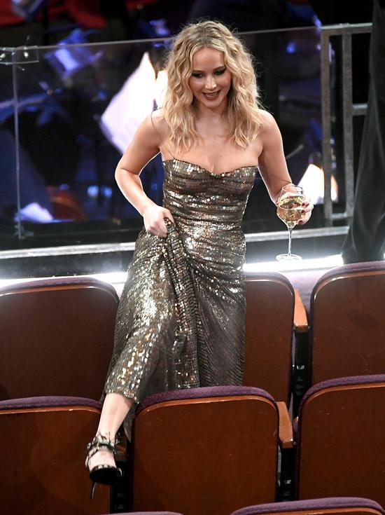 Trước khi lễ trao giải bắt đầu, Jennifer Lawrence cầm cốc rượu vang trèo qua các hàng ghế để tới chỗ ngồi của cô.