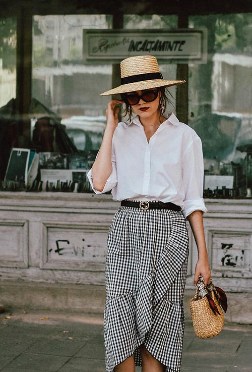 Set đồ trắng đen được kết hợp một cách nhuần nhuyễn giữa sơ mi phom dáng cơ bản đi cùng váy vạt xéo xinh xắn. Phụ kiện đi kèm là mũ nan, túi cói hợp mốt mùa hè.