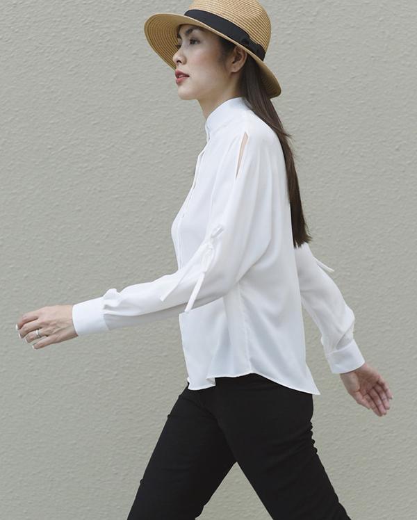 Mẫu áo sơ mi của Tăng Thanh Hà trở nên độc đáo hơn nhờ điểm nhấn đơn giản ở đường xẻ vai và trang trí dây thắt nút cho phần tay.