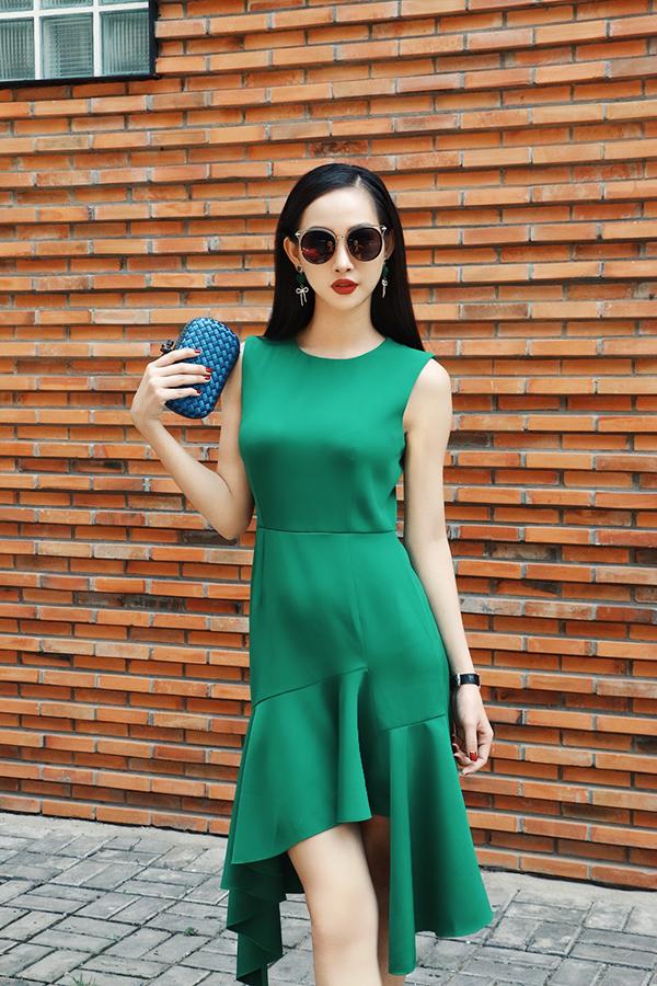 Váy vạt xéo tông màu xanh lá với phom dáng khai thác vẻ đẹp sexy chừng mực được kết hợp cùng clutch xanh dương và các phụ kiện mắt kính, đồng hồ da đen.