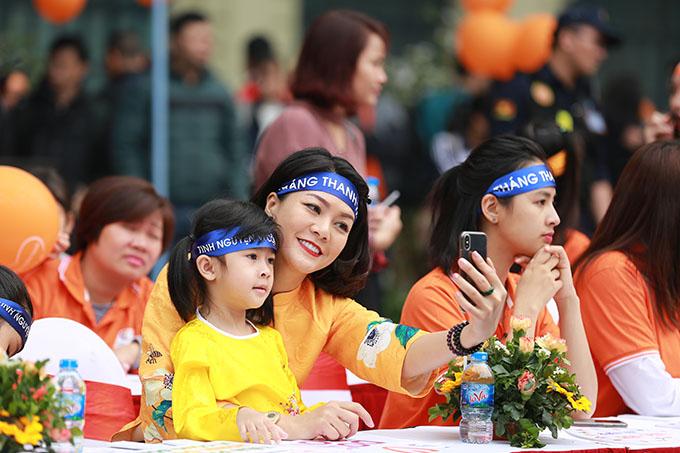 Hai mẹ con diễn viên Hoàng Xuân cũng có mặt từ sớm, diện áo dài vàng cam nổi bật và tích cực tham gia đi bộ cùng đoàn người tuần hành.