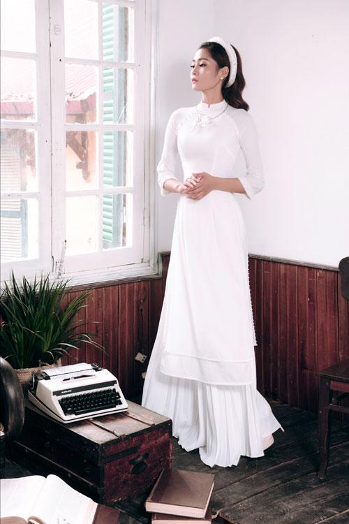 Chiếc áo dài cưới màu trắng viền hạt ngọc trai dọc hai bên tà, tay áo bằng vải voan mỏng phù hợp với những cô dâu có vóc dáng mình hạc xương mai.
