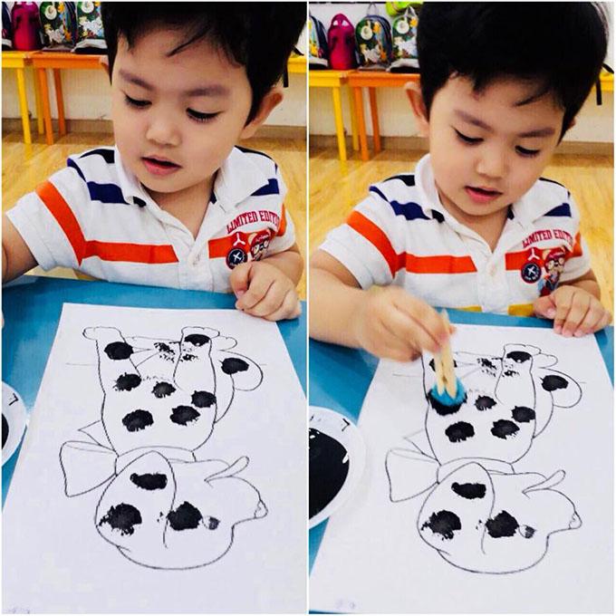 Kubi nhà Khánh Thi Phan Hiển say sưa tô màu cho chú chó đốm.