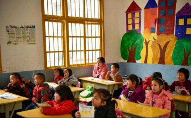 Chị Shi chăm chú học chữ cùng các em bé lớp mẫu giáolớn.