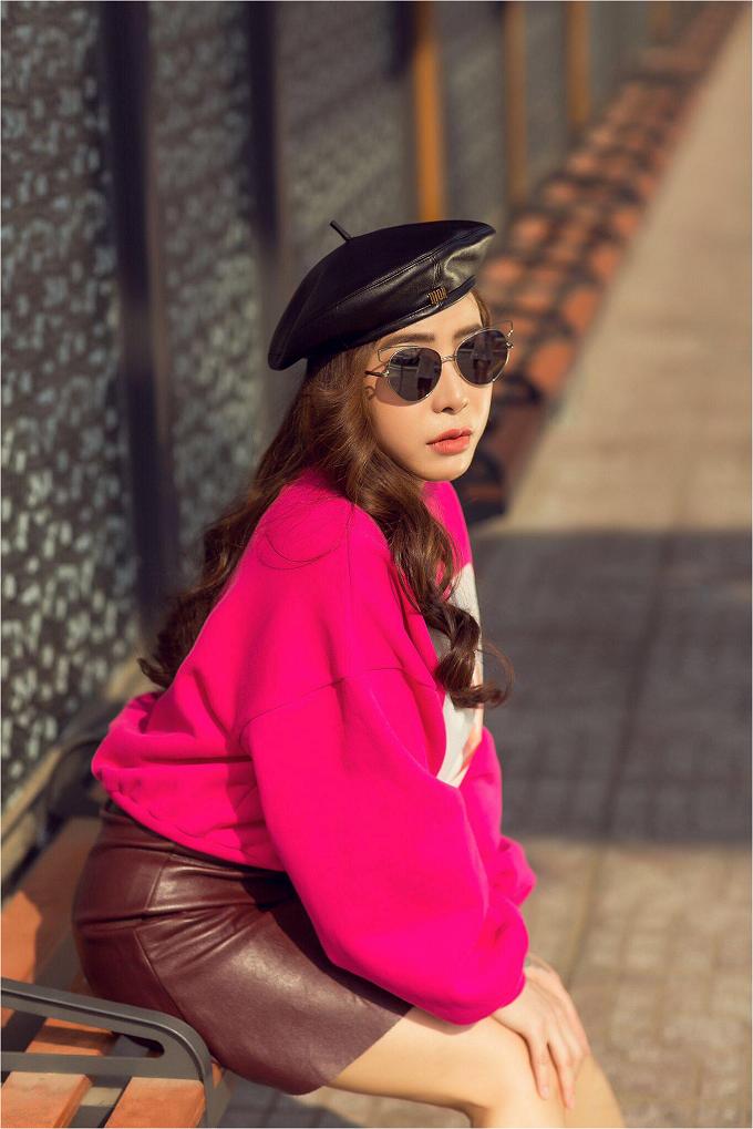 Vào những ngàyse lạnh, một chiếc áo nỉ hồng kết hợp với chân váy da cùng chiếc mũ kiểu quân đội của thương hiệu Diorgiúp cô nàng thêm cá tính và nổi bật.