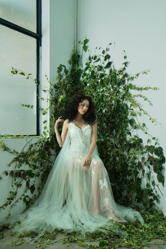 ới mái tóc xoăn bồng bềnh, nữ tính, Lilly diện váy ren kèm vạt xòe xuyên thấu. Cô xuất hiện như một nàng công chúa giữa khu vườn bí ẩn.