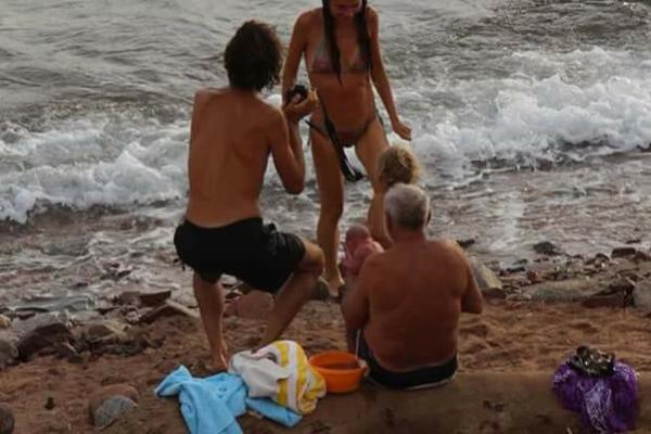 Người vợ bước lên từ dưới biển để gặp đứa con mới sinh của mình và gia đình. Ảnh: CEN