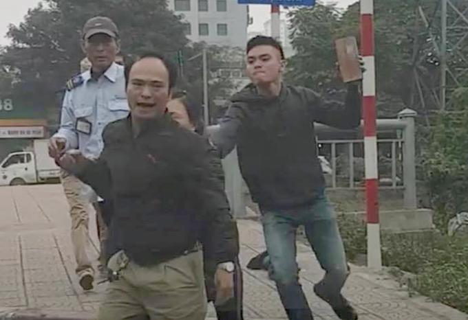 Phụ lái xe buýt cầm gạch đuổi theo tài xế xe tải. Ảnh cắt từ video.