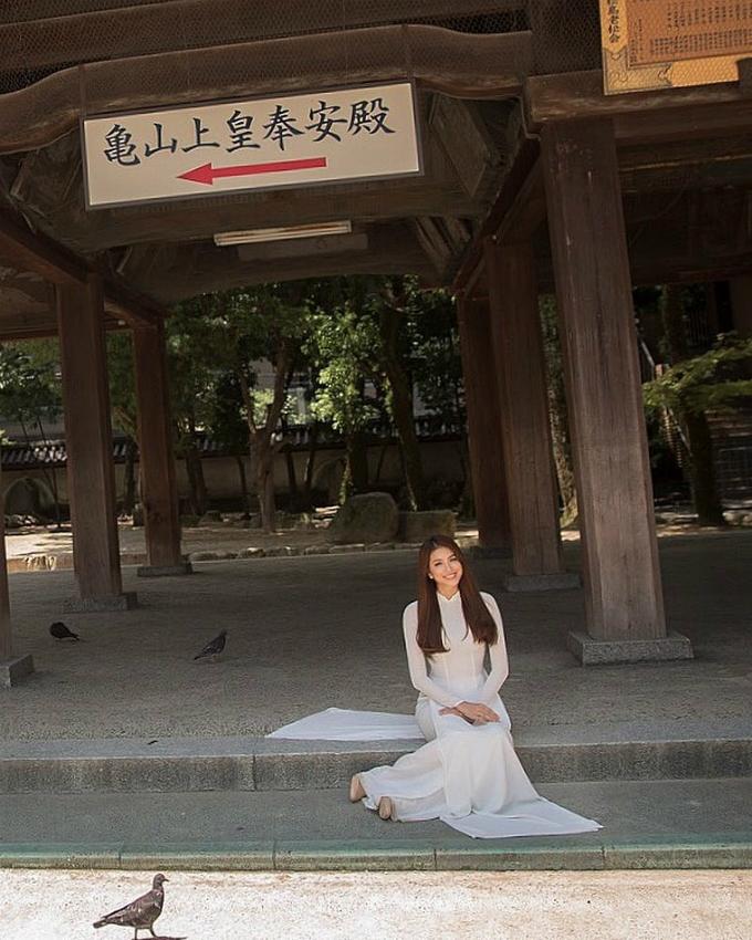 Phạm Hương diện áo dài mang đậm hình ảnh Việt Nam, ngồi bệt trước cửa một ngôi đền.