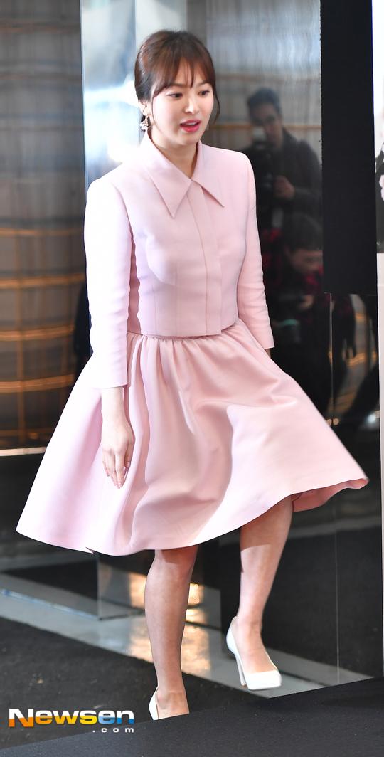 Song Hye Kyo dự sự kiện của thương hiệu mỹ phẩm mà cô là gương mặt quảng cáo năm 2018. Nữ diễn viên nổi tiếng xứ Hàn diện trang phục kín đáo, lịch thiệp, gương mặt trang điểm nhẹ nhàng và xinh xắn. Giữa tin đồn bầu bí, Song Hye Kyo đi giày cao gót, mặc váy xòe bó eo như một cách phủ nhận.