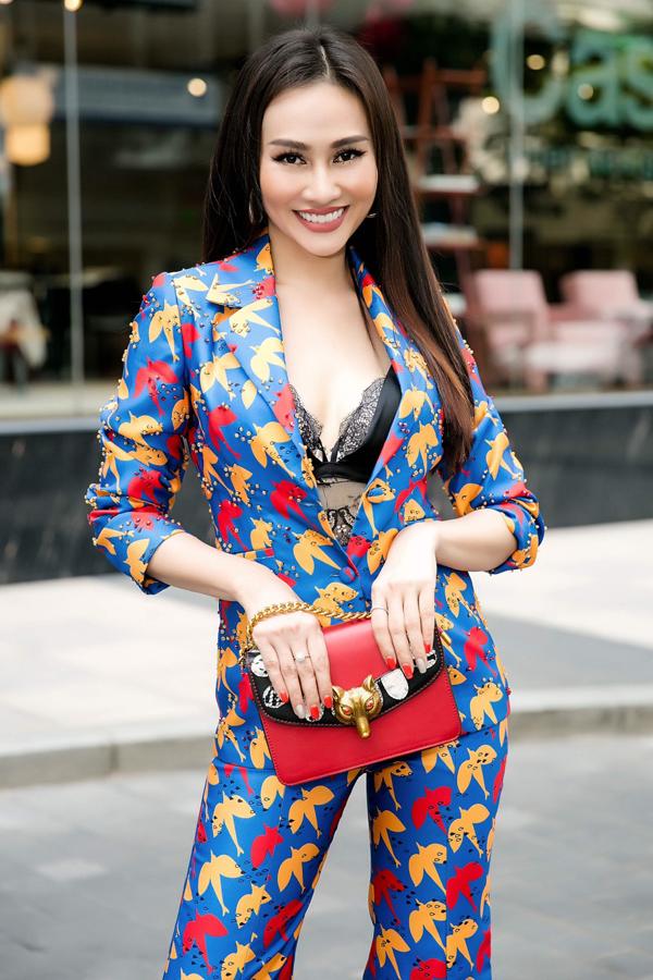 Cô khéo chọn phụ kiện túi xách hài hòa với bộ vest màu sắc.