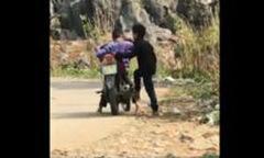 Hai cậu bé vùng cao giúp nhau tập đi xe máy