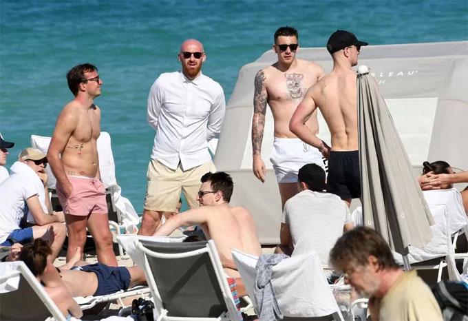 Đội trưởng Noble diện quần màu hồng, thư giãn với các đồng đội trên bãi biển.