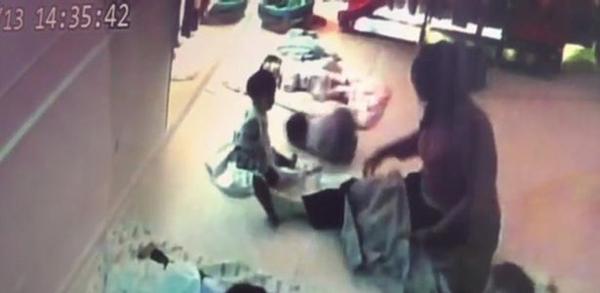 Bé gái bị bảo mẫu ném ngã dúi dụi xuống sàn nhà. Ảnh:AsiaWire