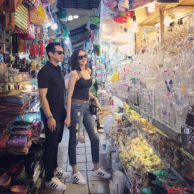 Vợ chồng Trúc Diễm - John Từ đi giày đôi, mặc trang phục đơn giản, xuống chợ sắm đồ.
