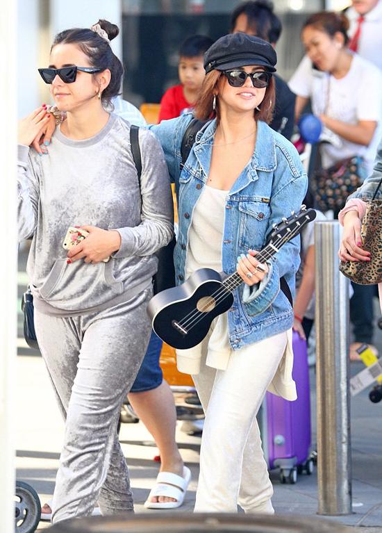 Cô xách theo cây đàn Ukulele, vui vẻ khoác vai người bạn tại sân bay Sydney.
