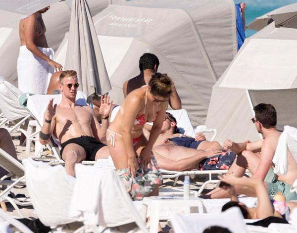 Joe Hart cố tỏ ra không bị xao nhãng bởi một cô gái ở bãi biển khi đang trò chuyện cùng các đồng đội trong lúc tắm nắng.