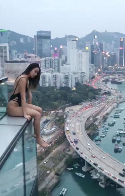 Cô gái thò cả hai chân xuống,thậm chí còn hơi nghiêng người ra ngoài khi ngồi ở mép tầng thượng.