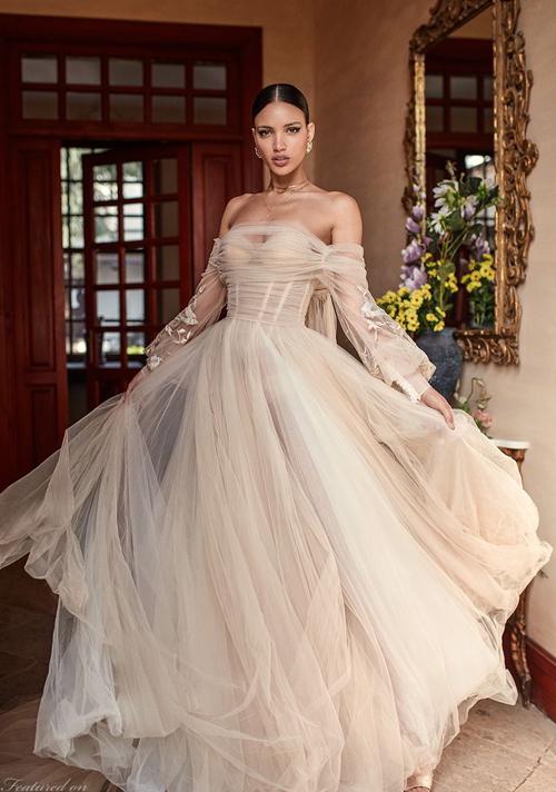 Váy cưới trễ vai dài tay bằng chất liệu voan lưới mềm mại, tone nude thời thượng.