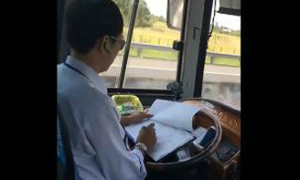 Tài xế ôtô vừa lái xe vừa ghi chép sổ sách
