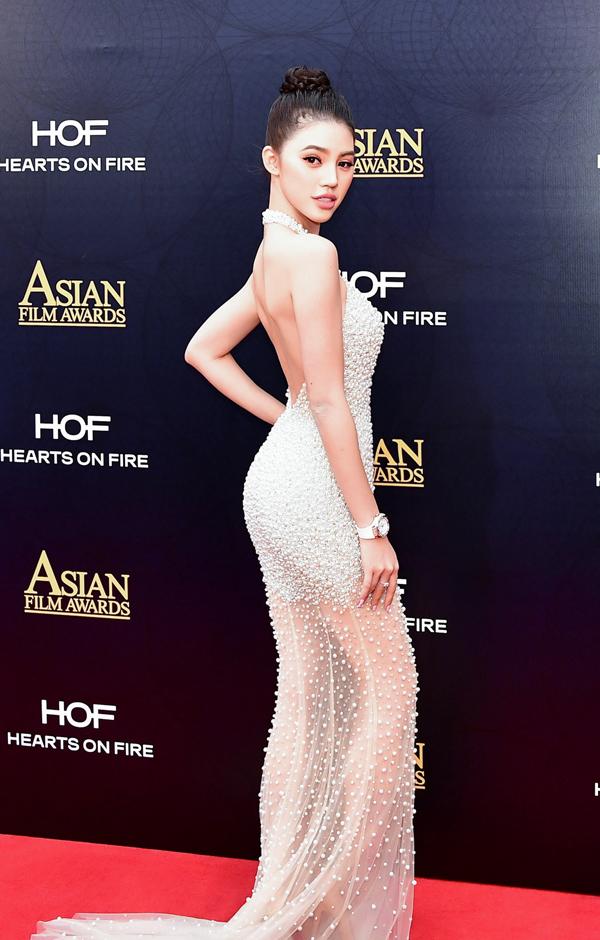 Mỹ nhân 21 tuổi diện thiết kế xuyên thấu, đính đá lấp lánh của nhà thiết kế Châu Phạm, tạo dáng kiêu sa trên thảm đỏ.