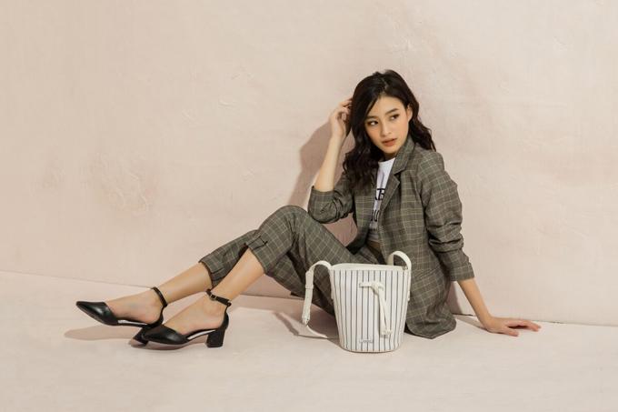 Một bộ blazer sọc ca rô với áo thun in chữ bên trong cùng đôi giày đếthấp màu đen và túi xách họa tiết kẻ sọc sẽ tạo nên tổng thể bắt mắt cho cô nàng công sở.
