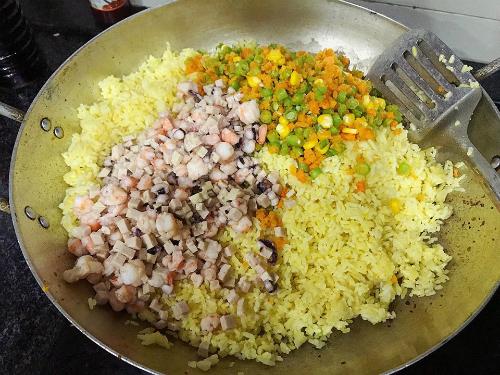 Trộn cơm, rau củ, tôm, giò nạc, bạch tuộc đều rồi chiên.