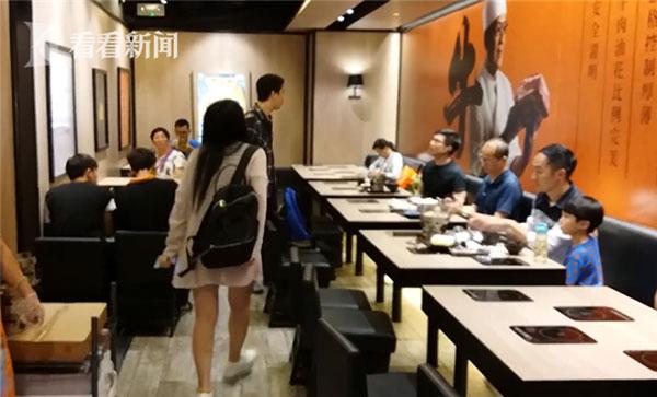 Người phụ nữ (đeo balo đen) hùng hổ mắng lại chàng trai (đang ngồi, đeo kính) vì bị anh này cáo buộc cho con tè vào cốc uống trà.