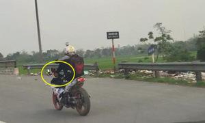 Thanh niên dùng chân lái xe máy trên đường quốc lộ