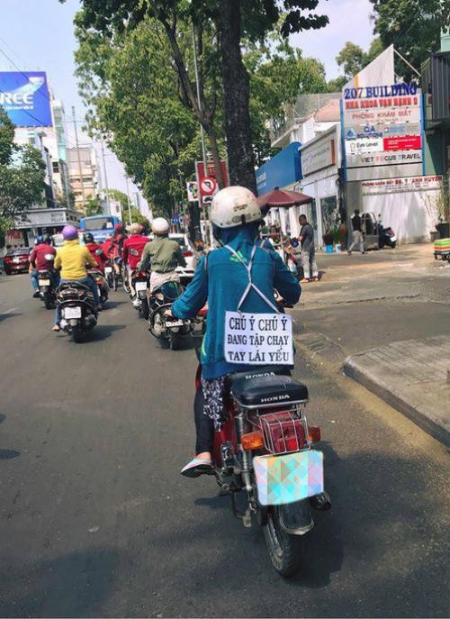 Người phụ nữ tập chạy xe máy đeo biển cảnh báo người đi đường.