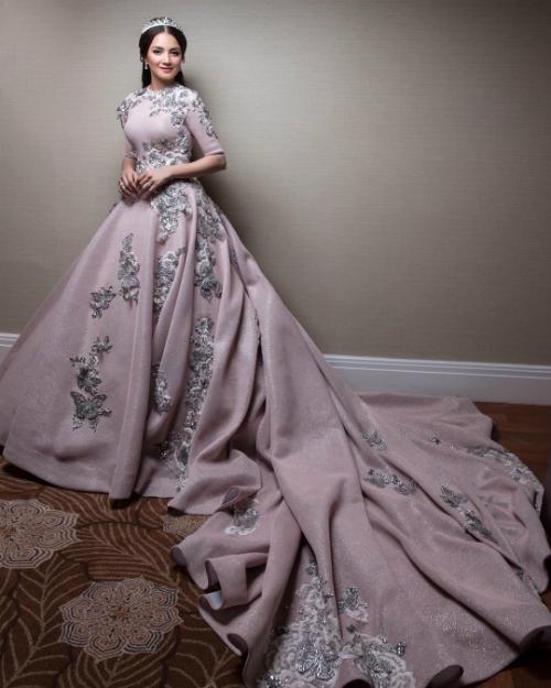 Cô dâu mặc hai chiếc váy cưới của nhà thiết kế Rizman Ruzaini, một chiếc màu hồng đính nổi họa tiết những cánh bướm với phần đuôi váy dài thướt tha.