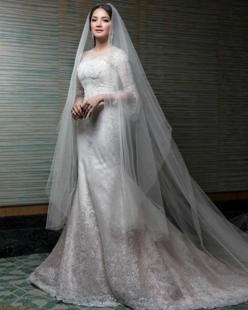 Chiếc váy trắng có phần chân màu ửng hồng còn lại được cô dâu mặc lúc cử hành hôn lễ chính thức. Dáng váy tay lửng kín đáo và thanh lịch.