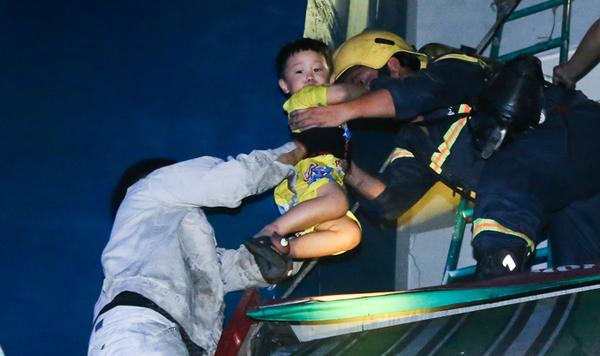 Một bé trai được cứu hỏa đưa xuống đất an toàn.