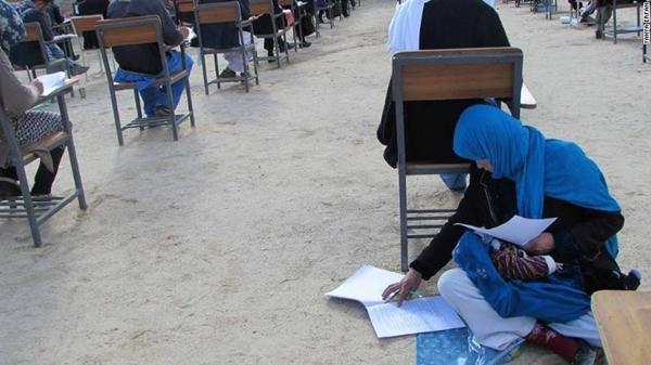 Hình ảnh Jahan ngồi bệt trên nền đất, làm bài thi với cô con gái trong lòng.