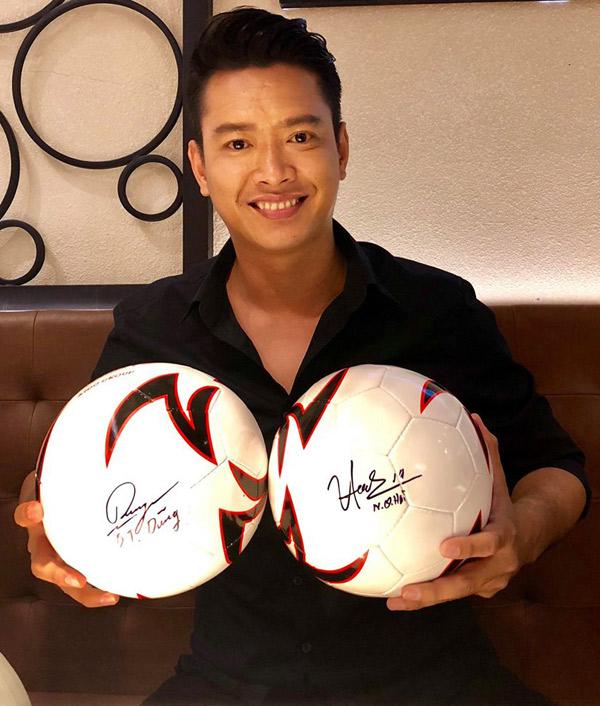 Siêu mẫu Hồ Đức Vĩnh hào hứng tham gia buổi gặp gỡ những người hùng của bóng đá Việt Nam. Anh khoe món quà là hai quả bóng có chữ ký của Tiến Dũng, Quang Hải.