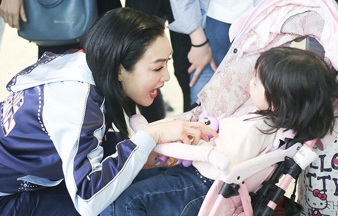 Chung Lệ Đề cưng nựng cô bé ngồi trên xe đẩy. Nữ diễn viên rất yêu trẻ con và cô cũng đã có 3 người con gái.