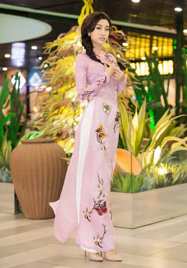 Mẫu áo dài màu hồng đầy nữ tínhc của Thuỷ Nguyễn là trang phục được Đỗ Mỹ Linh sử dụng khi đi chấm thi Duyên dáng áo dài. Cùng với tông màu dịu ngọt, hoạ tiết nhành hoa và cánh bướm đều được kết cườm thủ công một cách tỉ mỉ.
