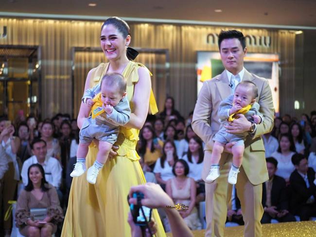 Hai em bé mải mê mút tay và tò mò nhìn ngó khắp nơi, trong khi bố mẹ giao lưu với các khán giả.